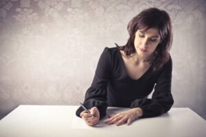 Woman writing disciplinary hearing letter